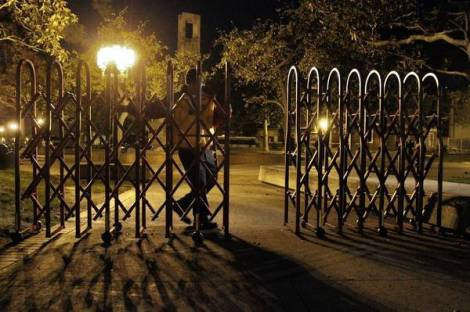 A guard closes a portable gate at USC under the new security precautions. (Lawrence K. Ho / Los Angeles Times)
